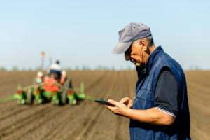 Farmer in field checking farm data